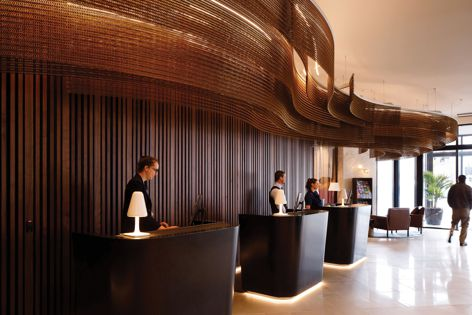 A custom ceiling installation of Spacemaile mesh in bronze adds warmth to the lobby at the Crowne Plaza hotel in Christchurch. Interior design: Designworks. Photography: Jason Mann.