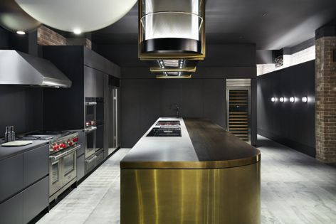 The demonstration kitchen and dining area is dominated by the extensive form of the kitchen island, overhung by custom Wolf rangehoods featuring bespoke brass metalwork.